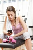 Smiling Woman Using Smart Phone At The Gym