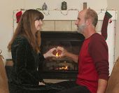 picture of cozy hearth  - A Married Couple Sit in Front of a Fireplace at Christmas  - JPG