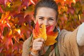 Happy Young Woman Hiding Behind Leaf While Making Selfie In Fron