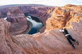 picture of bend  - photographer taking a picture of Horse Shoe Bend in Arizona belly crawling to cld edge of the cliff - JPG