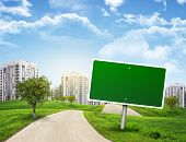 Blank green billboard and tree by road running through grassy hills towards city