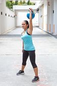 Beautiful sporty hispanic woman in blue  lifting blue kettlebell  for snatch routine outdoors