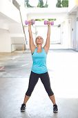 Back view of sporty woman holding pink barbell with both arms stretched out for shoulder strengthening, outdoors.