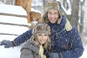 Portrait of happy young loving couple smiling at wintertime in snowfall.