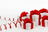 Gifts in white boxes with curly red ribbons isolated on white background