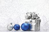 Decorative Christmas balls and gift on silver bokeh background