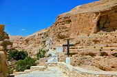 The road leading to the temple. Sacred George Hozevit's well-known monastery. The monastery is constructed to Vadi Kelt's gorges in vicinities of Jerusalem.  The guiding signpost - Black Cross