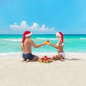 Happy Couple At Beach In Santa Hats Making Presents For Christmas