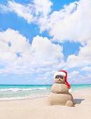 Smiling Sandy Snowman In Red Santa Hat On The Sea Beach