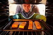 Man Putting Salmon Fillets Into Oven To Cook
