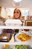 Woman Looking Inside Fridge Of Food And Choosing Sandwich