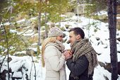 Young amorous couple celebrating Valentine�?�¢??s day in winter forest