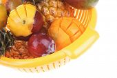 diet food - set of lot of tropical fruits include pineapple plum and mango in orange colander isolated over white background