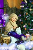 foto of knitted cap  - the girl in lilac jeans in a knitted cap and with a knitted scarf sits on a sledge near a Christmas fir - JPG