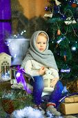 image of knitted cap  - the girl in lilac jeans in a knitted cap and with a knitted scarf sits on a sledge near a Christmas fir - JPG