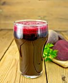 Juice beet in tall glass on board