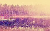 Vintage Filtered Picture Of Wooden Lake Pier At Sunset.
