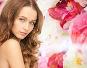 beauty, people and health concept - beautiful young woman with bare shoulders over pink floral background