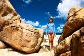 Woman at beautiful beach wearing rash guard. Seychelles, Curieuse island