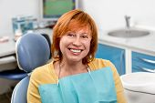 foto of dental  - Smiling senior woman with new dental implants sitting in the dental office - JPG