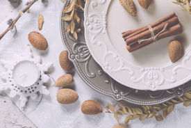 foto of christmas angel  - Two tone plates white and grey in a vintage style served for Christmas dinner with vintage cutlery and white napkin on a shabby white table with spices and other decorations - JPG