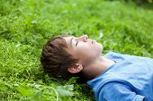 image of schoolboys  - Happy teenager lying on grass in park outdoor schoolboy - JPG