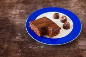pic of bonbon  - Piece of chocolate cake and bonbons on a plate on wooden table background - JPG