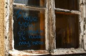 stock photo of abandoned house  - Old broken grunge part of weathered window of abandoned house with funny graffiti notice on glass - JPG