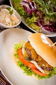 stock photo of bread rolls  - Tasty traditional cheeseburger with a ground beef patty topped with melted cheese and served with onion rings tomato and curly leaf lettuce on a round white bread roll close up view - JPG