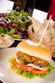 pic of bread rolls  - Tasty traditional cheeseburger with a ground beef patty topped with melted cheese and served with onion rings tomato and curly leaf lettuce on a round white bread roll close up view - JPG