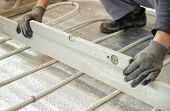 pic of spirit  - Man sets flat concrete floor with a ruler and spirit level - JPG