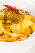 picture of nachos  - Bowl of crisp golden corn nachos with cheese sauce or dip and olives served as a starter or appetizer to a meal