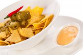 stock photo of nachos  - Bowl of crisp golden corn nachos with cheese sauce or dip and olives served as a starter or appetizer to a meal