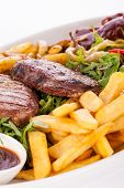 stock photo of leafy  - Wholesome platter of mixed meats including grilled steak crispy crumbed chicken and beef on a bed of fresh leafy green mixed salad served with French fries and chutney or BBQ sauce in a dish