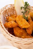 image of high calorie foods  - Crispy fried crumbed chicken nuggets in a wicker basket served as a finger food or appetizer with a creamy dip in a bowl alongside