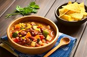 picture of sweet-corn  - Wooden bowl of vegetarian chili dish made with kidney bean carrot zucchini bell pepper sweet corn tomato onion garlic with tortilla chips in the back photographed with natural light  - JPG