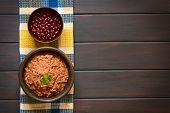 stock photo of kidney beans  - Overhead shot of a rustic bowl of homemade red kidney bean spread garnished with fresh coriander leaf a bowl of raw kidney beans above photographed on dark wood with natural light - JPG