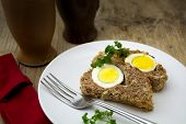 image of meatloaf  - slices of baked meatloaf with boiled eggs for Easter on rustic wooden background - JPG