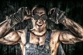 image of mines  - Portrait of a strong muscular man coal miner standing over dark grunge background - JPG