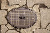 stock photo of manhole  - Manhole cover surrounded by pavement granite stones - JPG
