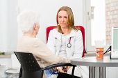 pic of geriatric  - Young female doctor sitting with pensioner in surgery consultation hour at desk - JPG