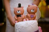 stock photo of three tier  - beautiful wedding cake with a teddy bear at the top - JPG