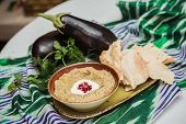 picture of dipping  - Traditional arabian eggplant dip baba ganoush with herbs and smoked paprika on a wooden background  - JPG