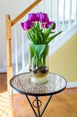 picture of stairway  - Purple tulips in a vase on mosaic table in hall near front door and stairway - JPG