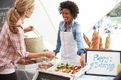 stock photo of marquee  - Female Bakery Stall Holder At Farmers Fresh Food Market - JPG