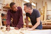 stock photo of carpenter  - Carpenter With Apprentice Planing Wood In Workshop - JPG