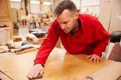stock photo of carpentry  - Carpenter Finishing Wood In Carpentry Workshop - JPG