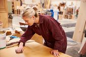 stock photo of carpentry  - Female Apprentice Finishing Wood In Carpentry Workshop - JPG