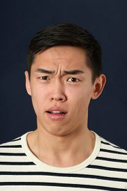 stock photo of disgusting  - Disgusted young Asian man looking at camera - JPG
