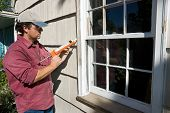 stock photo of air paint gun  - A Man Caulking An Outside Window To Insulate Against the Winter Weather - JPG